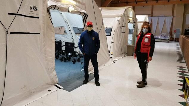 Deux personnes prennent la pose devant des tentes médicales installées dans une salle de banquet de Chisasibi.