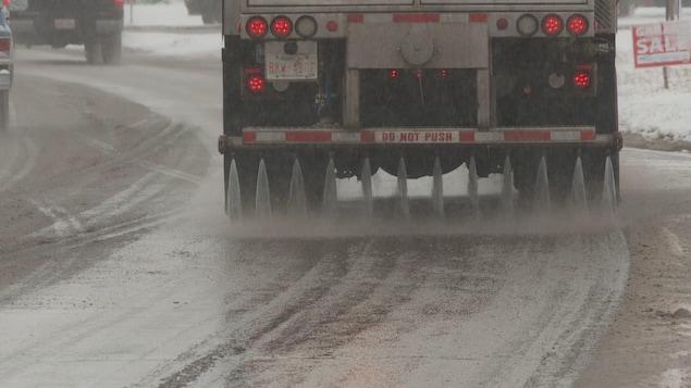 Un camion déverse un mélange liquide à base de chlorure de calcium sur une route.