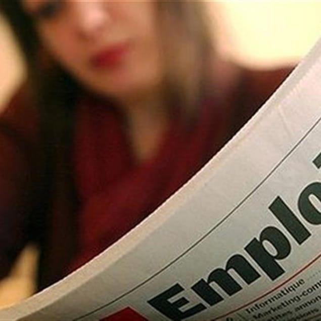 Femme lisant un journal pour de la recherche d'emplois