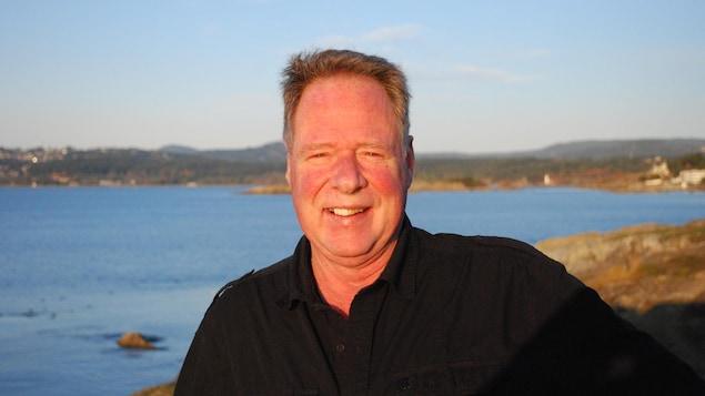 Un homme souriant devant un plan d'eau.