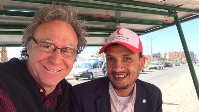 Roger Christen est assis à gauche et un représentant du Croissant-Rouge marocain est assis à droite, dans un véhicule de la compagnie Solar E-cycles.