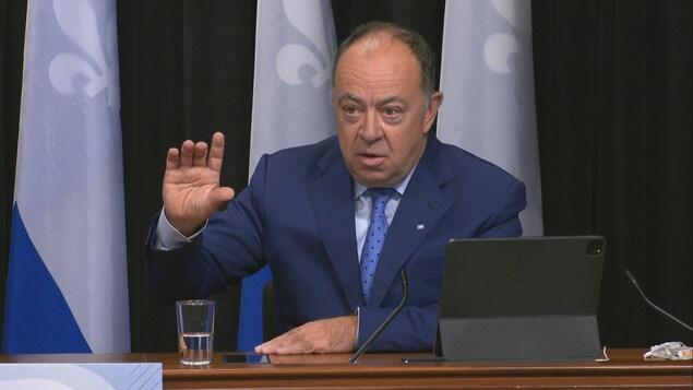 Christian Dubé devant des drapeaux du Québec, en conférence de presse.