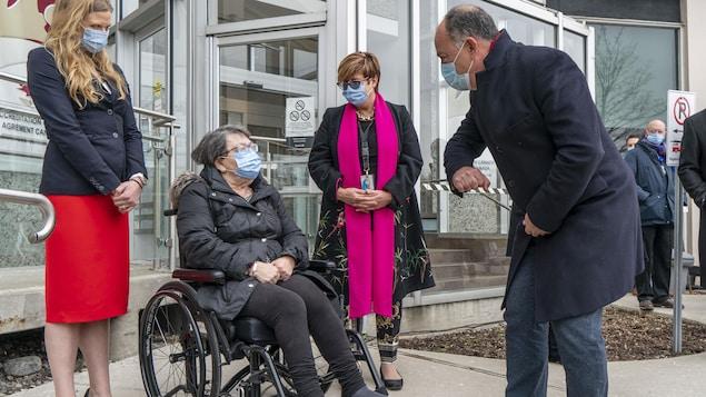 Christian Dubé se tient debout devant une femme en fauteuil roulant à l'entrée de l'établissement.