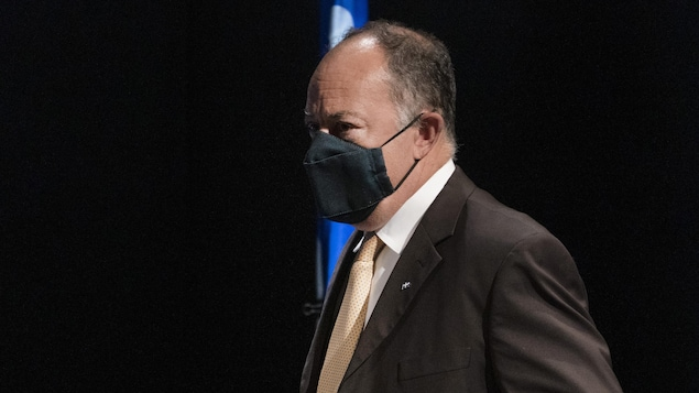 Le ministre de la Santé et des Services sociaux, Christian Dubé, debout et portant un masque à son arrivée à la conférence de presse.