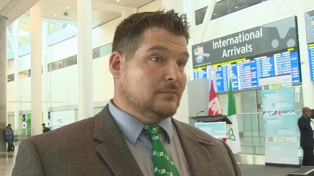 Photo d'un homme en complet portant une cravate avec des drapeaux franco-ontariens devant le tableau d'affichage des arrivées à l'aéroport.