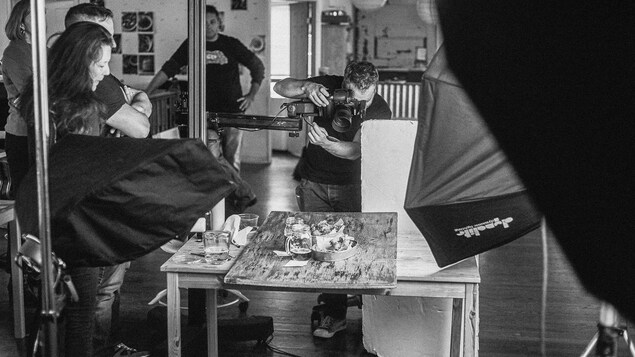 Photo en noir et blanc d'une session de photos en studio. Christian Lalonde est penché sur son objectif. Il fait une photo gastronomique avec des plats et deux bières dans des pots Masson avec poignées. L'équipe autour de lui le regarde travailler.