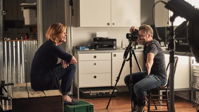 Le photographe Christian Lalonde sourit derrière son appareil photo. Son doigt est sur le déclencheur de l'appareil. Il est assis sur une chaise de bois. Une femme est assise devant lui sur une boîte de bois, les pieds déposés sur une caisse de plastique verte.