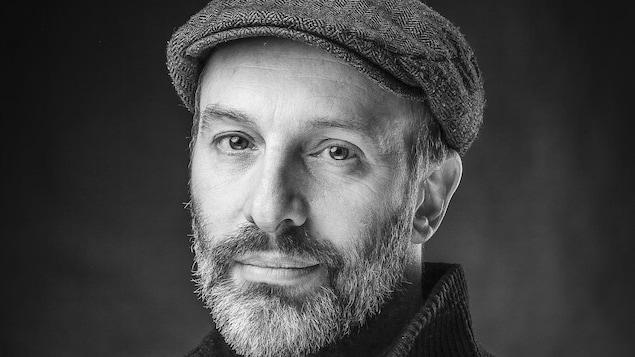 Le comédien et sculpteur Christian Michaud est ravi et étonné du succès de ses oeuvres. Un bel homme, fin quarantaine. Photo en noir et blanc.
