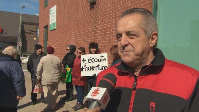 Le maire est interviewé alors que des résidents manifestent autour de lui.