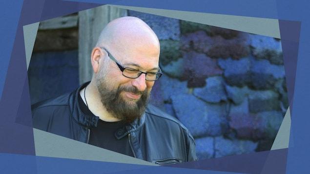 L'illustrateur Christian Quesnel regarde le sol, souriant, devant un mur de pierre bleuté.