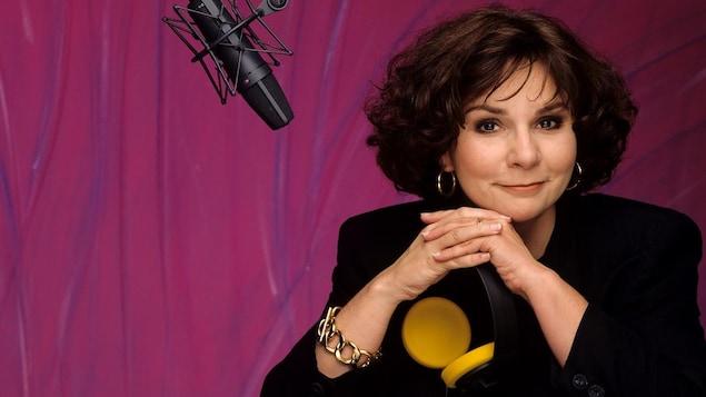 L'animatrice Christiane Charette posant près d'un micro avec des écouteurs à la main.