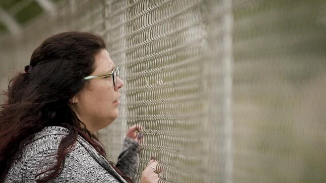 Christie-Anne Blondeau qui regarde à travers une clôturel'air triste.