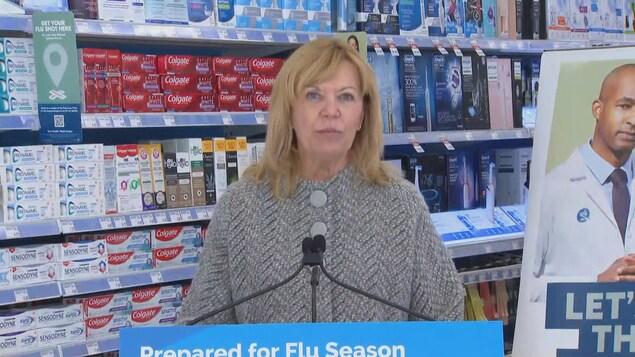 Christine Elliott devant un micro à un point de presse.