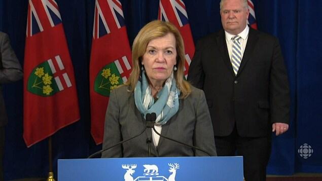 Mme Elliott parle à la tribune, devant le premier ministre Doug Ford.