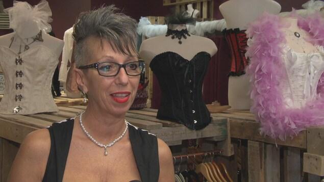 Christine Lamb, propriétaire de la boutique Le Corset, répond aux questions d'une journaliste dans sa boutique.