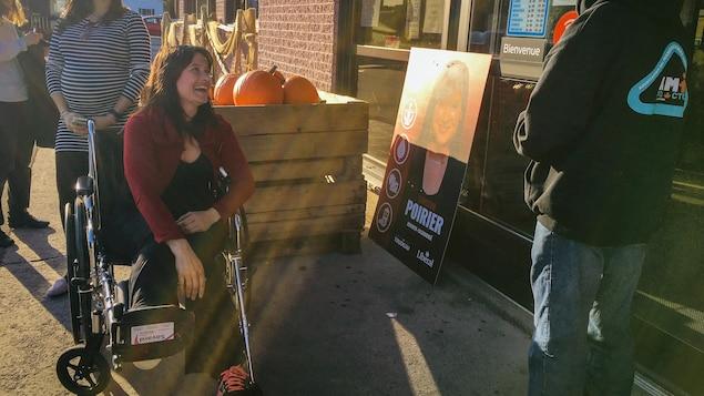 Christine Poirier dans sa chaise roulante devant des citrouilles.