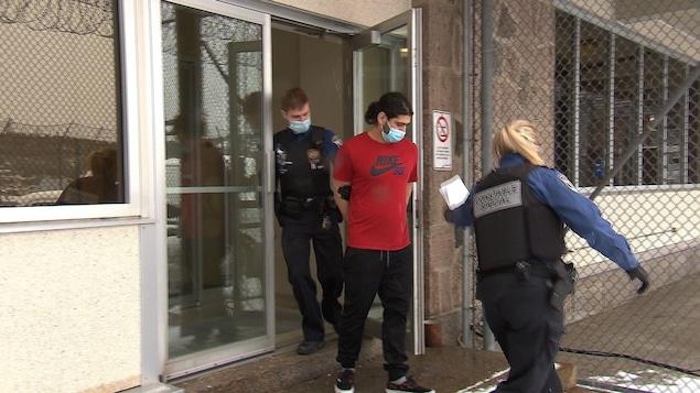 Un homme menotté est escorté par deux agents.
