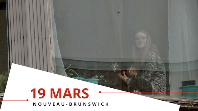 Une jeune femme joue de la guitare derrière une vitre.