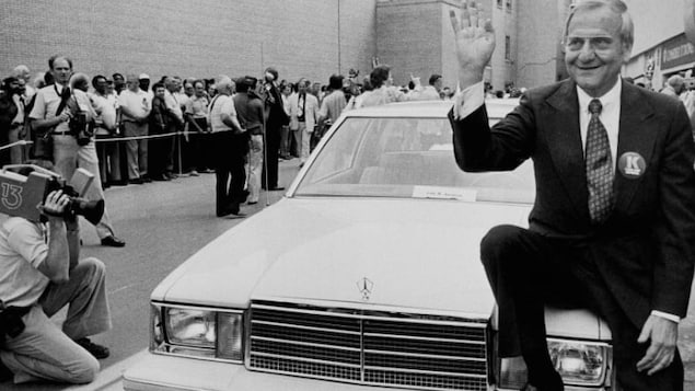 Lee Iacocca est assis sur une voiture et salue le public.