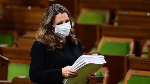 Chrystia Freeland, portant un masque et se tenant debout à la Chambre des communes, tient une pile de documents.