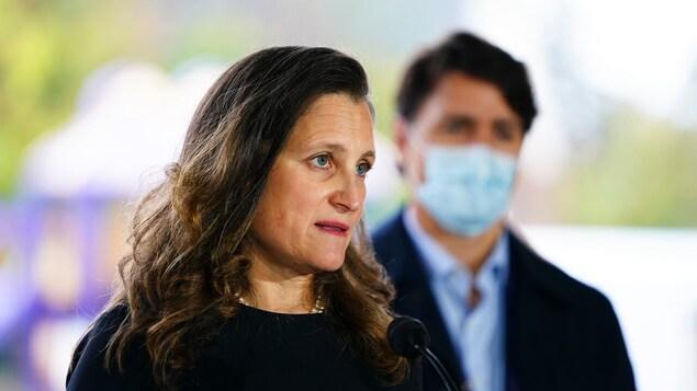 Nasa harap ng mikropono si Chrystia Freeland at nasa likod niya ang naka-mask na si Justin Trudeau.