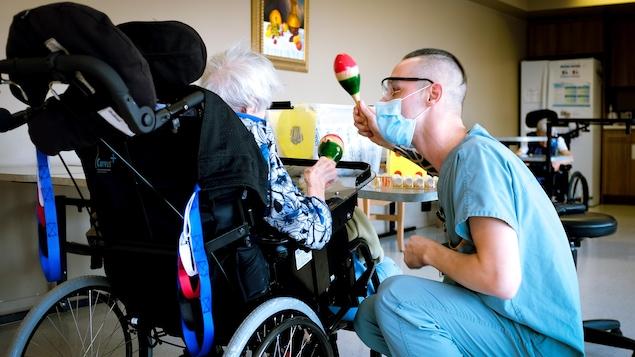 Un préposé masqué tient un maracas à côté d'une dame en fauteuil roulant vue de dos. Elle aussi tient un maracas.