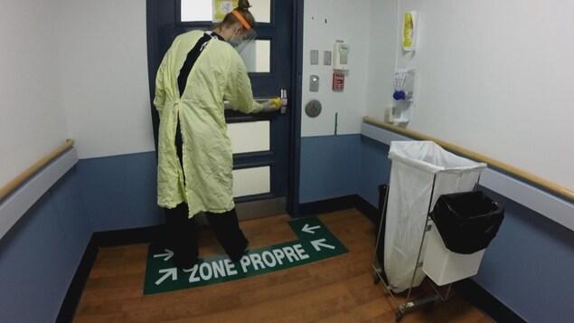 Une employée nettoie une porte.
