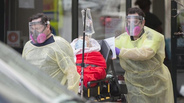 Deux personnes en habits de protection, avec des visières, accompagnent un patient sur une civière.