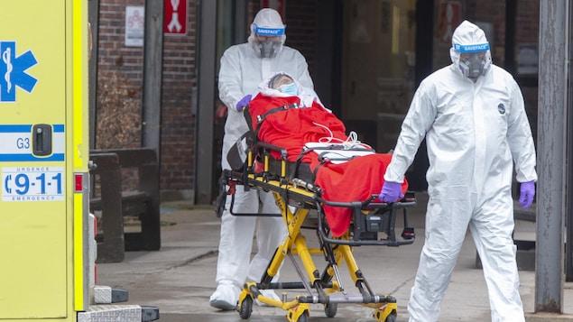 Des ambulanciers en combinaison transportent un malade sur une civière.
