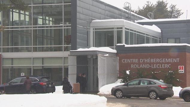Un édifice avec l'inscription «Centre d'hébergement Roland-Leclerc» affichée sur son mur extérieur. En hiver. Des automobiles sont stationnées devant.