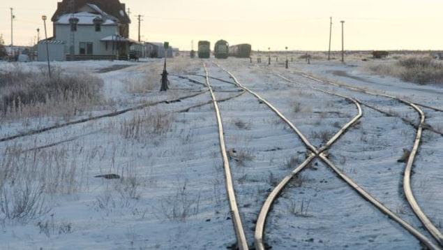 Des chemins de fer entourés de neige et des wagons au loin dans la ville de Churchill au Manitoba