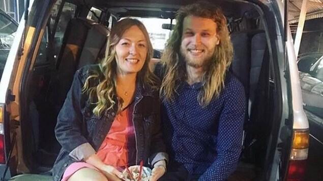 Le couple est assis à l'arrière d'une fourgonnette.
