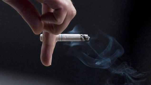 Une main tient une cigarette.