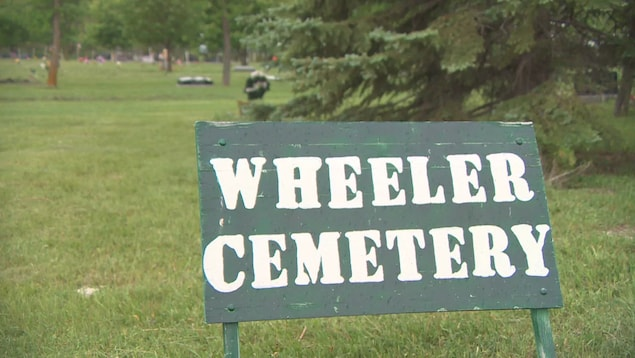 Un panneau de bois indiquant l'emplacement d'un cimetière.