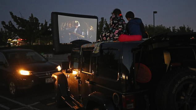 Deux amateurs de cinéma regardent un film sur leur toit de leur camion.