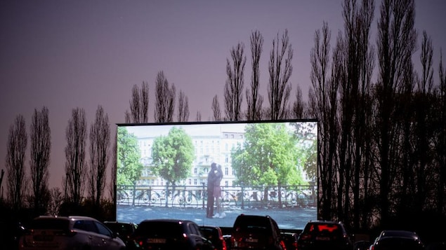 "KORNWESTHEIM, GERMANY - APRIL 06: Visitors sit in their cars as they watch ""Nightlife"" at the Autokino drive-in cinema during the coronavirus crisis on April 6, 2020 in Kornwestheim, Germany. While regular cinemas remain temporarily closed as part of overall measures to stem the spread of the virus, drive-in cinemas have in some German states been allowed to remain open, with the requirement that a maximum of two people occupy each car. An Autokino company spokeswoman said business is booming a"