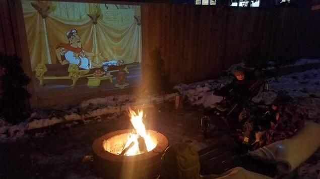 Deux enfants regardent un film près d'un feu.
