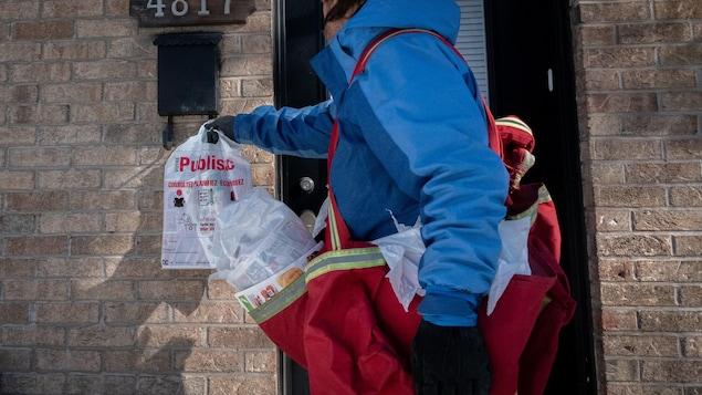 Un camelot accroche un Publisac à l'entrée d'une maison, à Montréal.