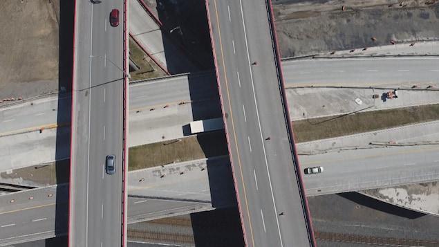 Vue en hauteur d'un échangeur. Trois véhicules circulent.
