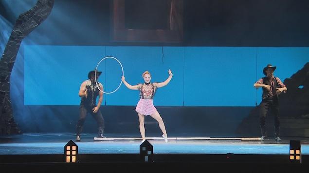 Femme avec un cerceau dans la main et deux cowboys à côté d'elle sur la scène.