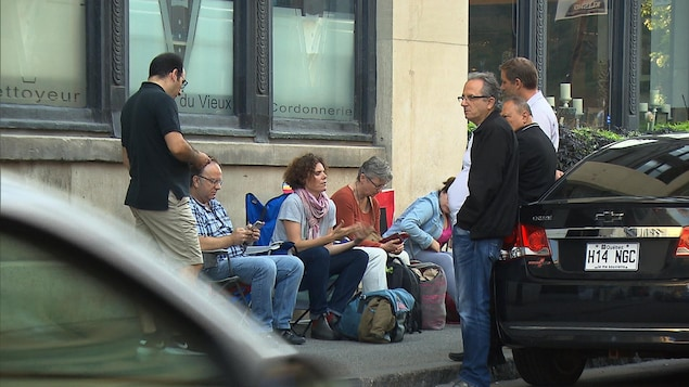 Des citoyens assis sur des chaises de camping sur un trottoir, à Montréal, devant un édifice.