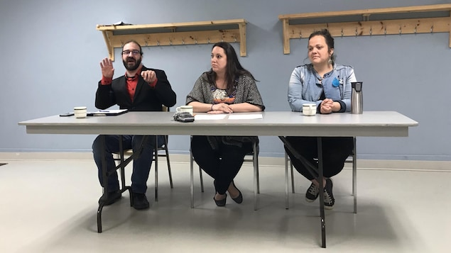 Un homme et deux femmes sont assis derrière une table durant un point de presse.