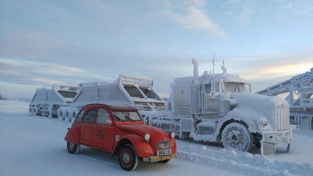 La 2 CV garée près d'un gros camion couvert de neige et de glace.