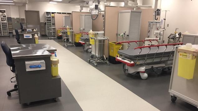 Des civières prêtes à recevoir des patients à l'urgence de l'Hôpital Charles-Le Moyne, devant des postes d'observation, entourées de machines et de moniteurs.
