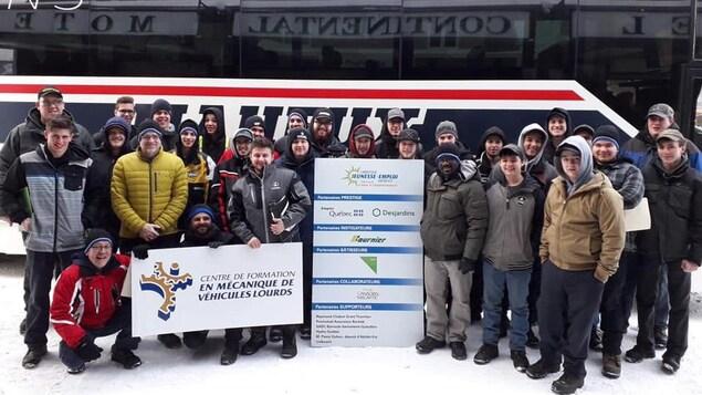 De jeunes adultes sont réunis autour d'une affiche du Centre de formation en mécanique de véhicules lourds et du Carrefour jeunesse emploi d'Abitibi-Est, devant un autobus Maheux.
