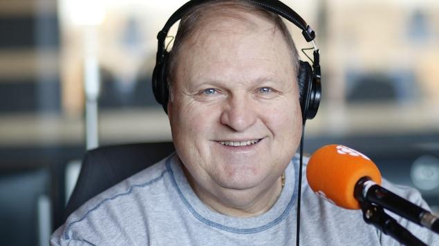 Un homme souriant dans un studio de radio.