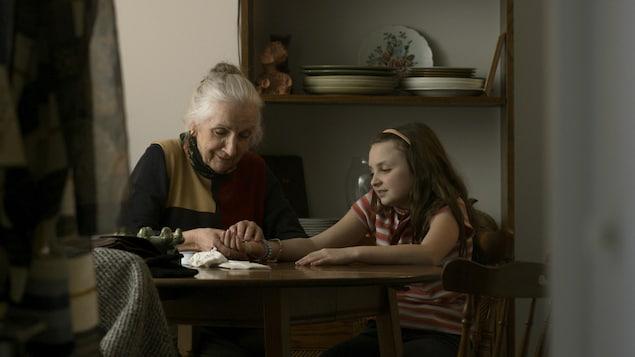 La grand-mère et sa petite-fille sont assises à une table et se touchent les mains.
