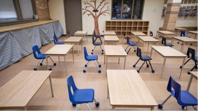 Une classe vide avec de longues tables de travail et des chaises bleues