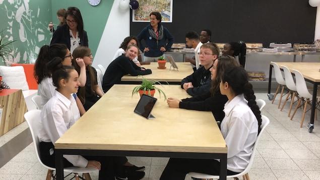 Des élèves sont assis autour d,une table dans une salle de classe.