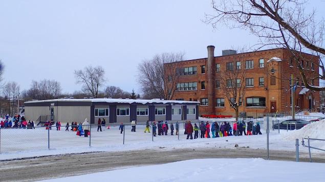 La Commission scolaire des Affluents a fait installer des classes modulaires à l'École Saint-Louis à L'Assomption. Sur la photo, des enfants du primaire jouent devant les locaux modulaires.
